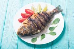Dorado fritado dos peixes com cal, tomates e espinafres Alimento de mar fotografia de stock royalty free