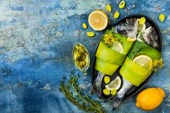 Dorado in prei in bakselvorm klaar wordt verpakt aan het koken, voorbereiding op rustieke blauwe achtergrond met olie, kruiden en Royalty-vrije Stock Foto's