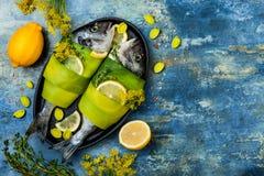 Dorado in prei in bakselvorm klaar wordt verpakt aan het koken, voorbereiding op rustieke blauwe achtergrond met olie, kruiden en Stock Afbeeldingen