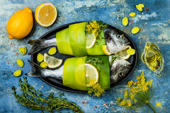 Dorado wrapped in leek in baking form ready to cooking, preparation on rustic blue background with oil, herbs and spices. Top view stock images