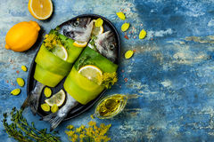 Dorado wrapped in leek in baking form ready to cooking, preparation on rustic blue background with oil, herbs and spices. Top view royalty free stock image