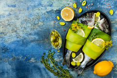 Dorado wrapped in leek in baking form ready to cooking, preparation on rustic blue background with oil, herbs and spices. Top view royalty free stock photos