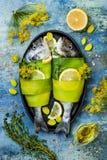 Dorado zawijał w leek w pieczenie formie przygotowywającej gotować, przygotowanie na nieociosanym błękitnym tle z olejem, ziele i Zdjęcie Stock