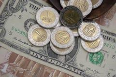 Dorato ed argenti le monete di 1 metallo della sterlina egiziana su una carta moneta del dollaro di U.S.A. Fotografie Stock Libere da Diritti