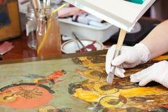Doratura del restauratore sull'icona con il burnisher dell'agata Immagini Stock Libere da Diritti