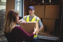 Doręczeniowy kierowca wręcza pakuneczek klient na zewnątrz samochodu dostawczego Obrazy Royalty Free