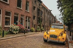 Elegant brick street with typical houses, plant and vintage yellow car in Dordrecht. Stock Photography