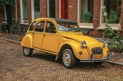 Elegant brick street with typical houses, plant and vintage yellow car in Dordrecht. Stock Images