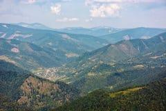 Dorf auf Abhangwiese mit Wald im Berg bei Sonnenaufgang Stockfotografie