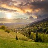 Dorf auf Abhangwiese mit Wald im Berg bei Sonnenuntergang Stockbild