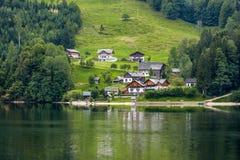 Dorf auf einem Hügel nahe einem See, Alpen Berge, Österreich Stockbild