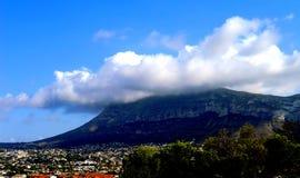 Dorf an einem Berg mit weißen Wolken Lizenzfreie Stockfotos