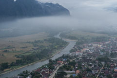 Dorf mit Fluss und Berg im Nebel Stockfoto