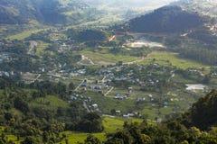 Dorf mit Reisfeldterrassen in einer grünen Gebirgstalvogelperspektive stockbilder