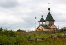 Dorf Unitsa, Republik von Karelien, Russland, am 28. Juli 2011: Peter und Paul Church im Bau, auf Bank von Unitskaya-Golf von Stockfotografie