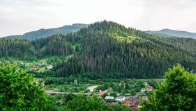 Dorf unter dem Berg nahe dem Fluss lizenzfreie stockfotografie
