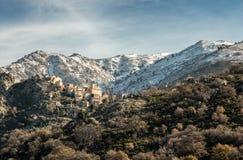 Dorf von Speloncato in Korsika mit Schnee bedeckte Berge Stockfoto
