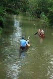 Dorfbewohner rudern ein traditionelles Boot in den Stauwassern lizenzfreies stockbild