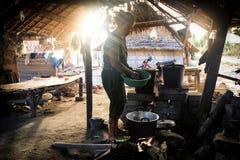 Dorfbewohnerarme kochen Mahlzeit unter grundlegendem Schutz lizenzfreie stockfotos