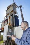 Dorfbewohnertechniker-Schreibenslesung des Strommeters auf Klemmbrett Stockbild