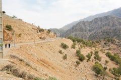 Dorffrauen, die auf Schotterweg vom alten kurdischen Dorf in den Bergen gehen Stockfoto