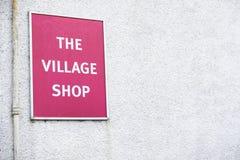 Dorfgeschäfts-Zeichenrot auf weißem Wandhintergrund lizenzfreies stockbild