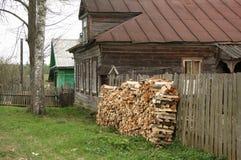 Dorfhaus mit Woodpile Stockfotos