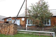 Dorfhaus in modernem Russland Ein braunes Haus mit einem hellen Dach hergestellt vom Schiefer Nahe dem Haus gibt es Brennholz Lizenzfreie Stockfotografie