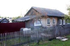 Dorfhaus in modernem Russland Ein braunes Haus mit einem hellen Dach hergestellt vom Schiefer Nahe dem Haus gibt es Brennholz stockbild