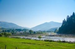 Dorflandschaft auf Hintergrund von Bergen lizenzfreie stockfotos