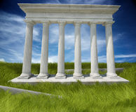 Doric columns ruins. Six white doric columns on a marble base on a bright morning in a grassy field royalty free illustration