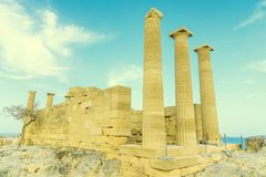 Doric temple of Athena Lindia on Acropolis of Lindos Rhodes, Greece. Front view of columns and walls. near tree grows. Doric temple of Athena Lindia on Acropolis stock image