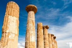 Dorische Säulen des Heracles-Tempels in Agrigent mit blauem Himmel und Wolken im Hintergrund stockbilder