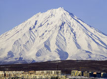 Dormant volcano. Covered with a snow and small northern town on Kamchatka stock photography