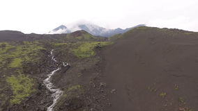 Dormant volcano. The river flows from the mountains stock video footage