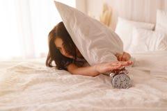 Dorment trop longtemps la femme se r?veillant arr?tant le r?veil photographie stock