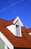 Dormer. And red roof against bright blue sky Stock Image