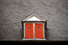 Dormer with red shutters. Close up of a dormer with red shutters on an old slate roof Stock Photography