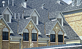 Dormer Roof Tops. View of multiple dormer roof tops with patterned gray roofing and brick trim Royalty Free Stock Image