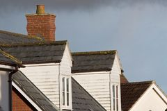 Dormer roof windows. Loft structures on modern town house buildi Stock Images