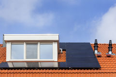 Dormer and solar panels. On a red tile roof Stock Photos