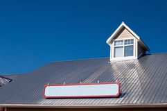 Dormer window on metal roof. Dormer window and store sign  on shiny aluminum roof Stock Photos