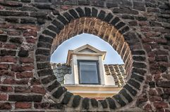 Dormer window of an old house. Photographed through an oval wall opening Royalty Free Stock Photo
