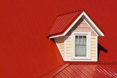 Dormer window on red roof. Colorful dormer window on a metal roof Stock Photo