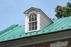 Dormer window on roof. Single dormer window on the old sloping green copper roof of a house Royalty Free Stock Photography
