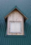 Dormer with windows on the dark green roof Stock Photography