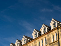 Dormer Windows in Terraced Houses. Dormer windows in a row of terraced houses against a deep blue sky. Aberystwyth, Wales, UK royalty free stock images