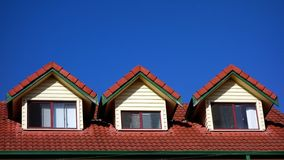 Dormer Windows. Three dormer windows on modern residential building, with red tiles and deep blue sky Stock Photos