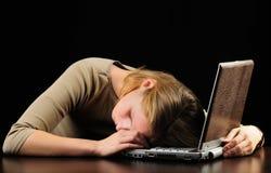 Dormido caido de la mujer joven sobre trabajo sobre la computadora portátil Foto de archivo