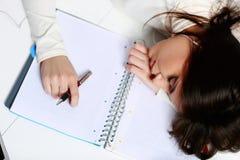 Dormido caido estudiante cansado en la tabla Fotos de archivo
